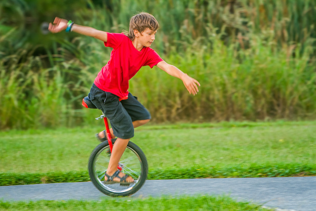 ジャパンボックス | A boy riding a unicycle in the greenery.